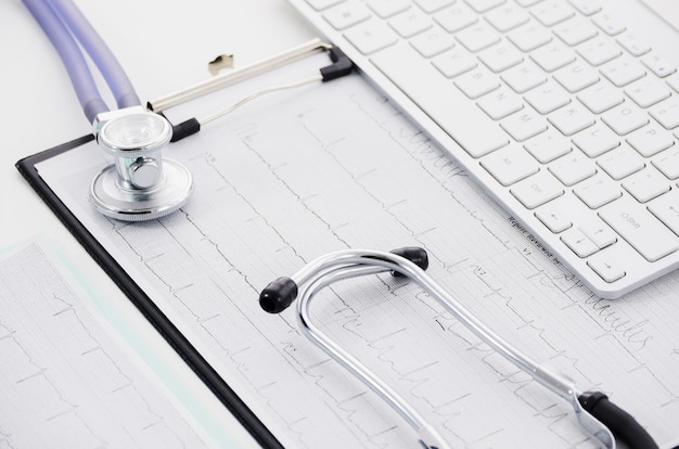 Stethoscope on ecg paper graph and laptop on white backdrop