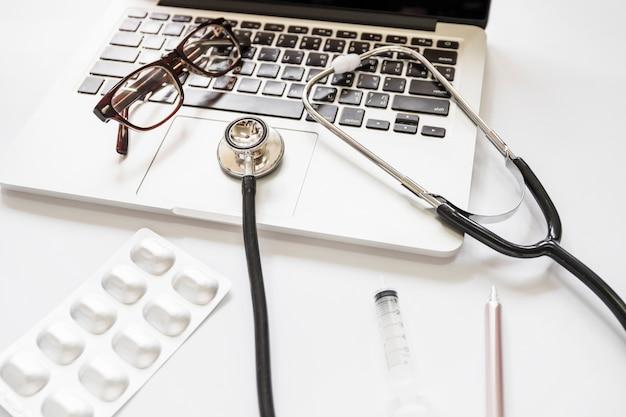 Stethoscope and eyeglasses on laptop keypad with medicine pack; syringe and pen on white background