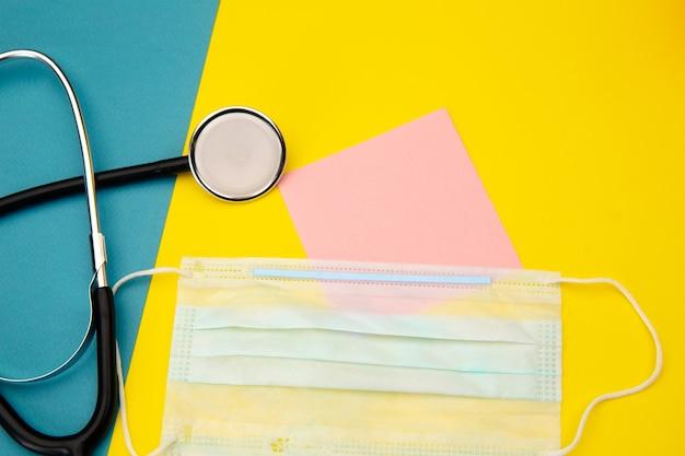 カラフルなテキスト用の聴診器、フェイスマスク、ピンクの付箋。