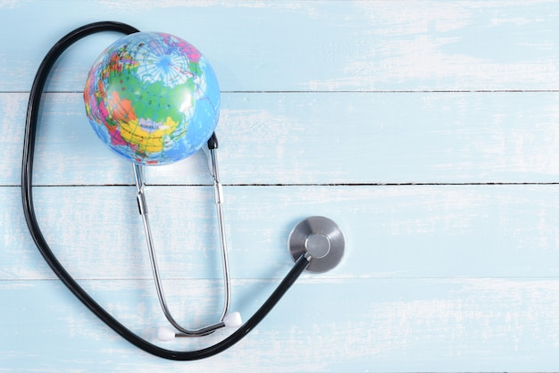 Stethoscope and globe on blue and white pastel wooden background. healthcare and medical concept.