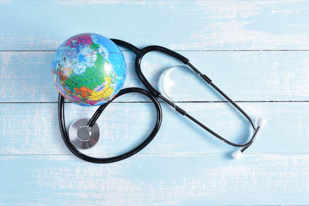 Stethoscope and globe on blue and white pastel wooden background.