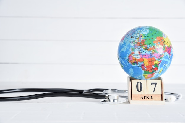 Stethoscope and globe with april 7 text wooden block calendar on white wooden background.