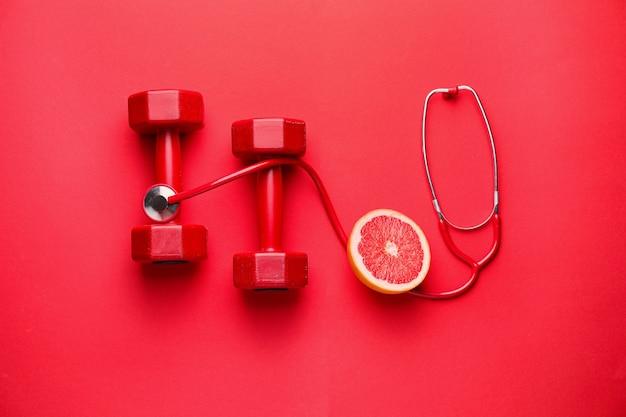 Стетоскоп, грейпфрут и гантели на цветном фоне