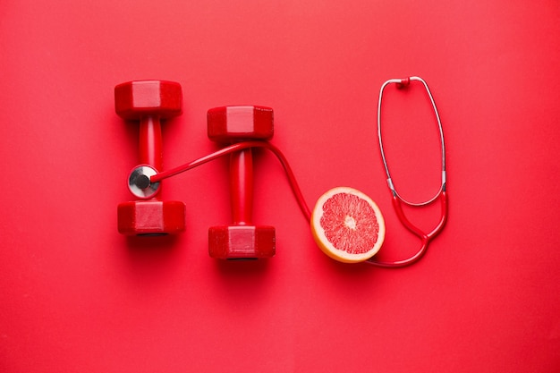 Stethoscope, grapefruit and dumbbells on color background