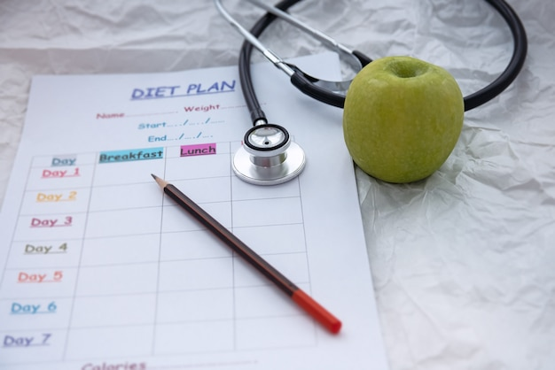 The stethoscope and green apple put beside blurred diet schedule plan