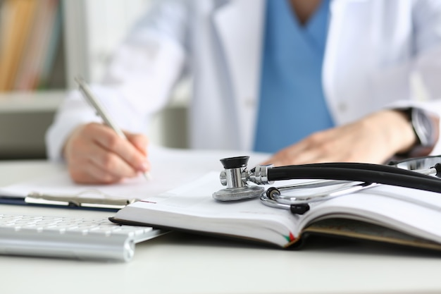 Stethoscope head lying on medical forms closeup while medicine doctor working in background.