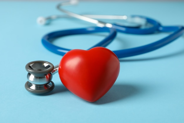Stethoscope and heart on blue surface, close up