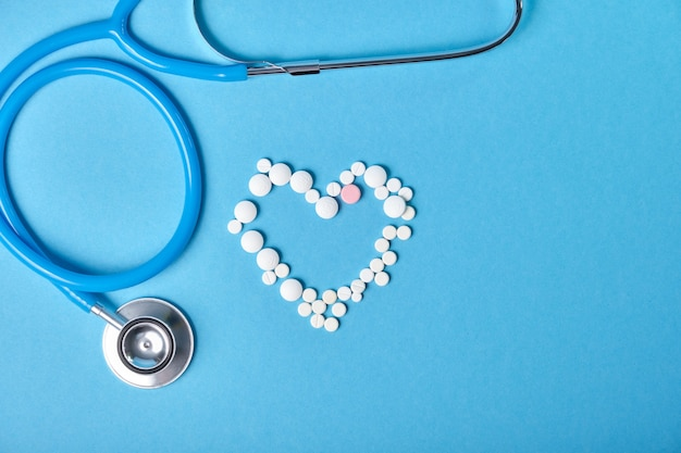 Stethoscope and heart from pills on blue background, cardiology concept