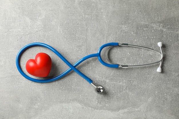 Stethoscope and heart on grey background, top view. healthcare