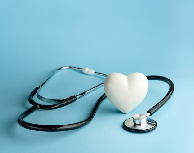 Stethoscope and heart shape on a blue background with copy space
