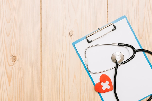 Stethoscope and heart with cross on clipboard