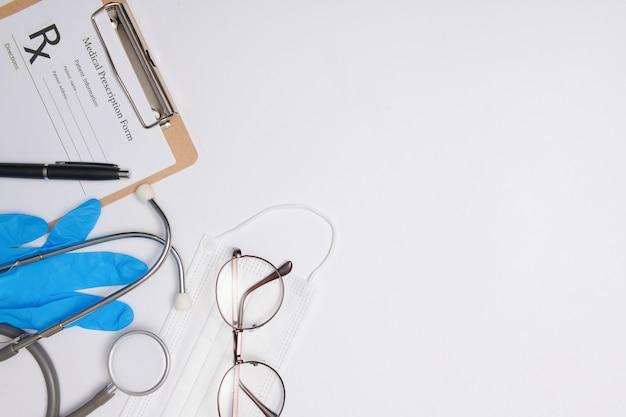 医師の机の聴診器、医療の概念。コロナウイルスcovid-19。白い机の上に聴診器、眼鏡、フェイスマスク。ウイルス、コロナウイルス、インフルエンザ、風邪、病気に対する保護。フラットレイトップビュー