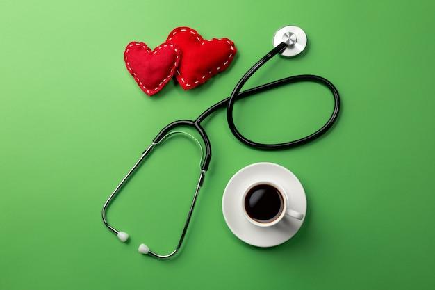 Стетоскоп в столе врачей с чашкой кофе и сердцем. вид сверху.