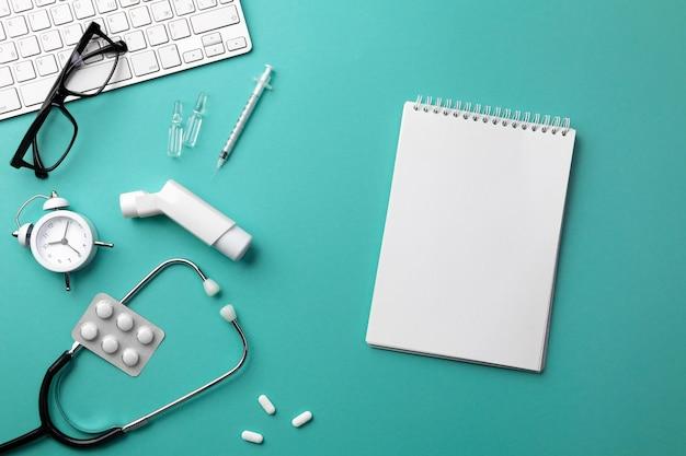 キーボード、目覚まし時計、眼鏡、吸入器、注射器、アンプル、吸入器、錠剤を備えた医師の机の聴診器。テキストの場所を含む上面図。