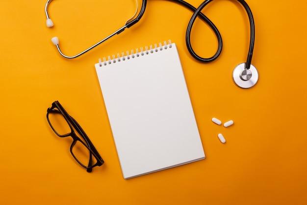 ノートと錠剤を備えた医師の机の聴診器。テキストの場所を含む上面図。