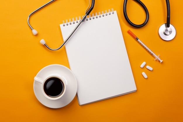ノートブック、コーヒーカップ、錠剤を備えた医師の机の聴診器。テキストの場所を含む上面図。