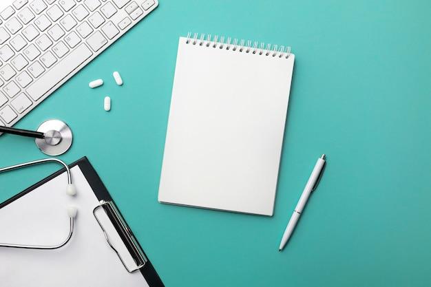 ノートパソコン、ペン、キーボード、マウス、錠剤を備えた医師の机の聴診器。テキストの場所を含む上面図。