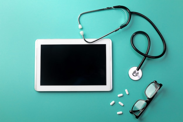 タブレット、眼鏡、丸薬を備えた医師の机の聴診器。テキストの場所を含む上面図。