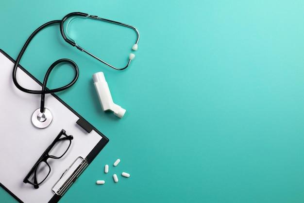 Стетоскоп в столе врачей с таблеткой, ингалятором и таблетками. вид сверху с местом для текста.