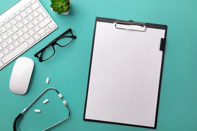 タブレット、ペン、キーボード、マウス、ピルを備えた医師の机の聴診器。テキストの場所を含む上面図。