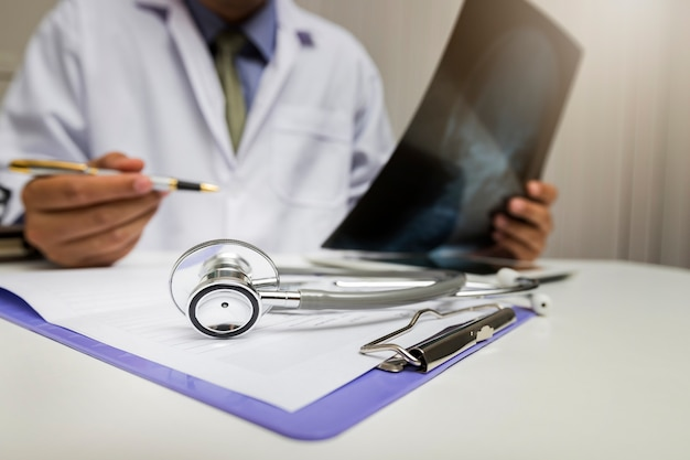 Stethoscope is lying on the clipboard near a doctor consults patient.
