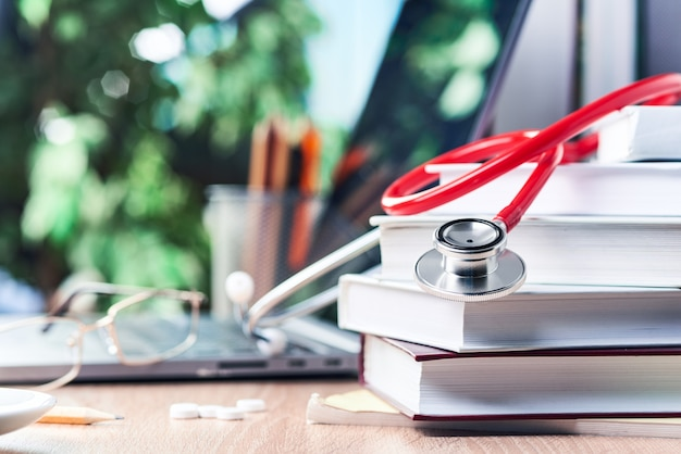The stethoscope is lying on medical books,