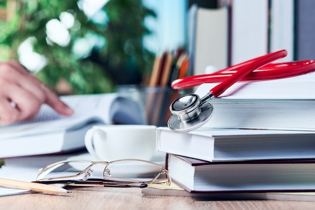 The stethoscope is on top of medical books, and a man's hand is pointing at a book