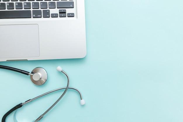 파란색 배경에 고립 된 청진 기 키보드 노트북 컴퓨터입니다. 현대 의료 정보 기술 및 소프트웨어는 개념을 발전시킵니다. 컴퓨터 및 가제트 진단 및 수리. 평면 위치 평면도
