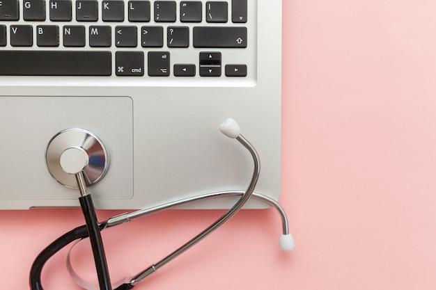 분홍색 배경에 고립 된 청진 기 키보드 노트북 컴퓨터입니다. 현대 의료 정보 기술 및 소프트웨어는 개념을 발전시킵니다. 컴퓨터 및 가제트 진단 및 수리. 평면 위치 평면도