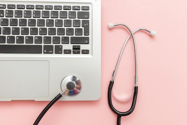 청진 기 키보드 노트북 컴퓨터 분홍색 배경에 고립입니다. 현대 의료 정보 기술과 소프트웨어는 개념을 발전시킵니다. 컴퓨터 및 가제트 진단 및 수리. 평면도 평면도