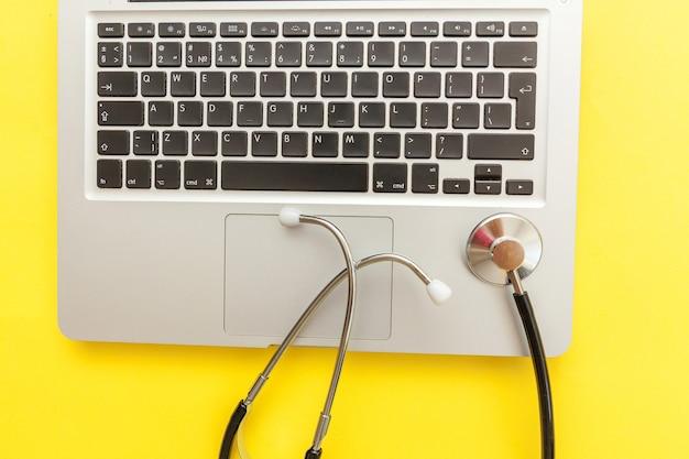 노란색 배경에 고립 된 청진 기 키보드 노트북 컴퓨터입니다. 현대 의료 정보 기술 및 소프트웨어는 개념을 발전시킵니다. 컴퓨터 및 가제트 진단 및 수리. 평면 위치 평면도