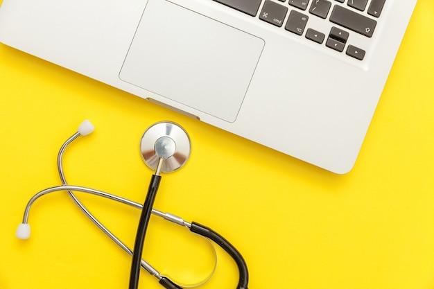 노란색 배경에 고립 된 청진 기 키보드 노트북 컴퓨터입니다.