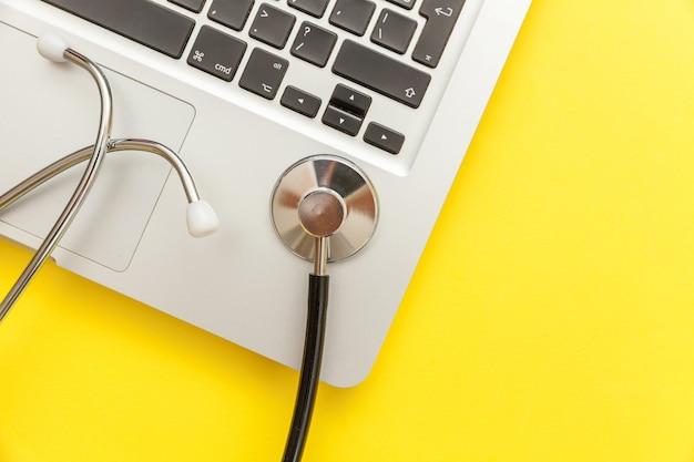 노란색에 고립 된 청진 기 키보드 노트북 컴퓨터