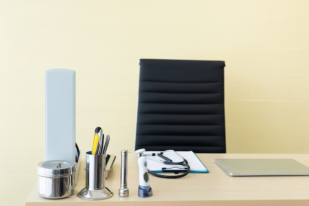 Stethoscope and labtop and other medical object on table of doctor.