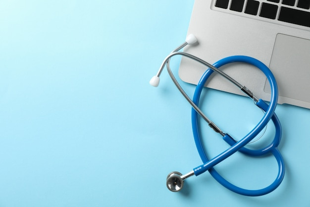 Stethoscope and laptop on blue background, space for text