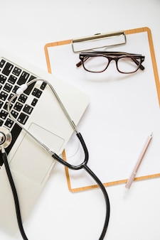 Stethoscope over the laptop and clipboard with eyeglasses and pen on white background