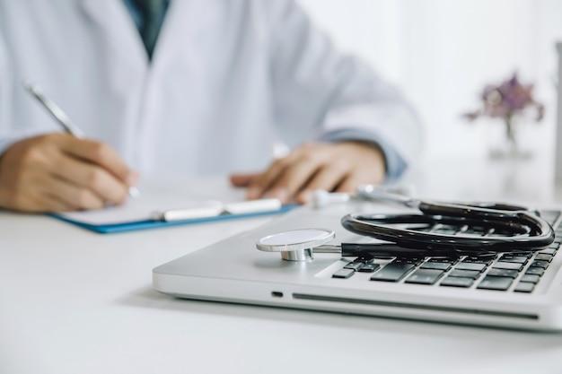 Stethoscope and laptop on desk,doctor working in hospital writing a prescription