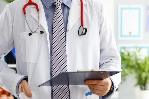 Stethoscope lying on male doctor chest in office