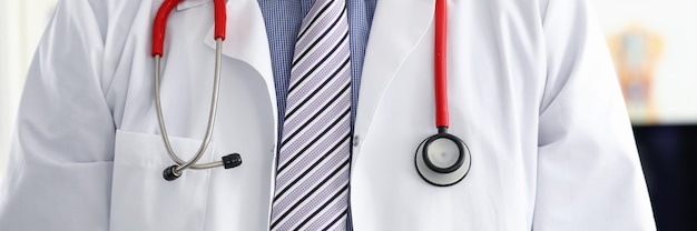 Stethoscope lying on male therapeutist doctor chest