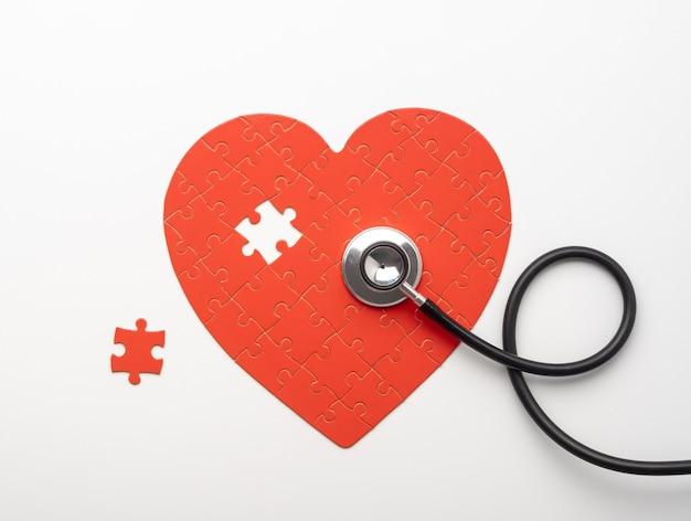 누락 된 조각으로 심장 모양의 퍼즐에 누워 청진 기