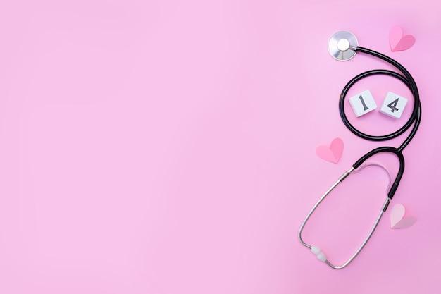 파스텔 바탕에 핑크 하트와 청진 기 의료 장비. 사랑으로 건강 관리. 발렌타인 데이