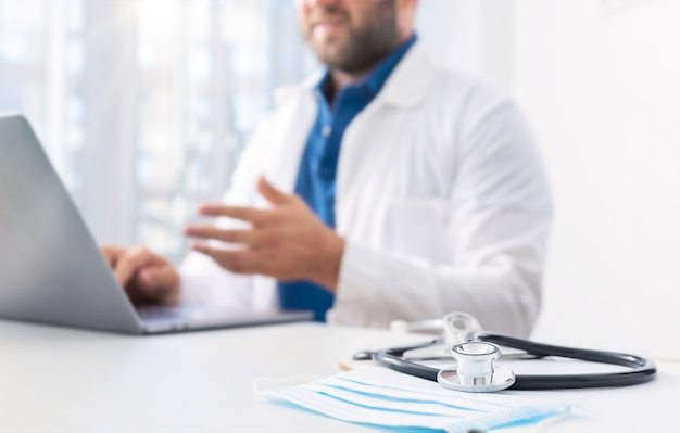 Stethoscope and medical mask on the doctors desk in the background. doctor conducts an online patient consultation using computer