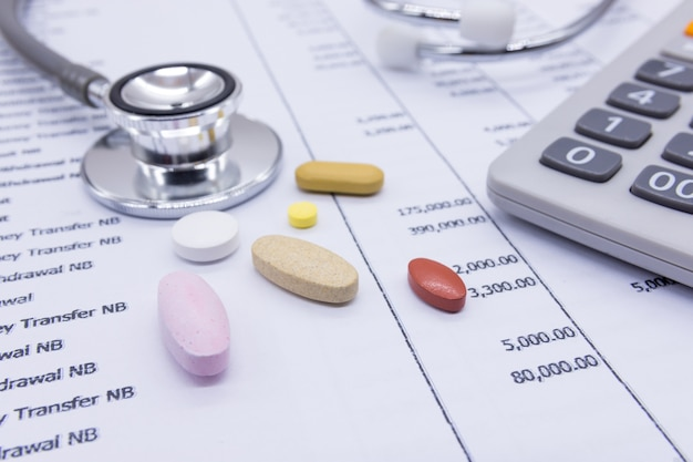Stethoscope and medicine on bank statements background, concept financial health.