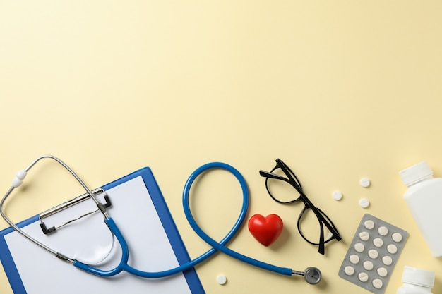 Stethoscope and medicines on yellow background, top view. doctor workplace