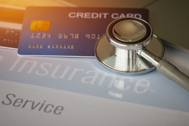 Stethoscope on mock up credit card with number on cardholder in hospital office
