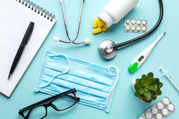 Stethoscope on notepad with medicines over blue backdrop