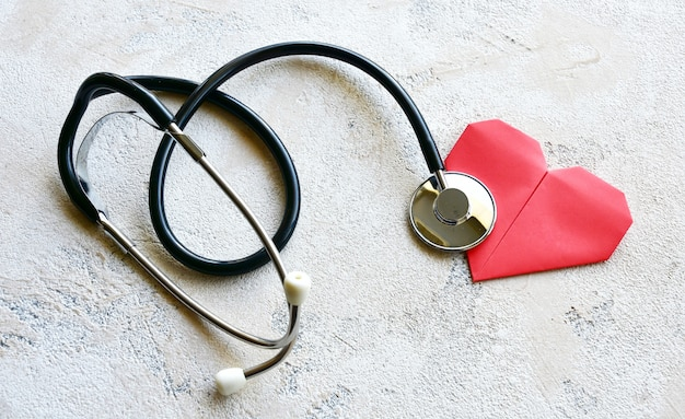 Stethoscope and origami paper red heart on a stone background. top view.