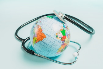 Stethoscope over the globe on blue background