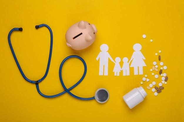 Стетоскоп, семья бумажной цепи, копилка и таблетки на желтом, концепция медицинского страхования