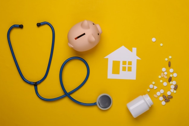 Stethoscope, paper house, piggy bank and pills on yellow, health insurance concept